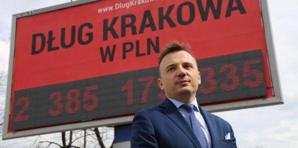 Łukasz Gibała na tle licznika długu Krakowa